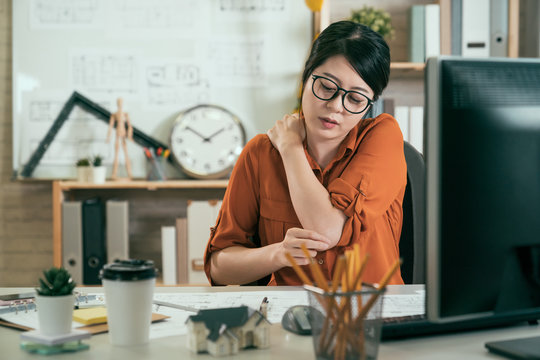Young asian korean woman employee suffer shoulder pain concept office syndrome. unhappy tired female architect worker massage hurting neck sitting at desk long time staring computer screen blueprint