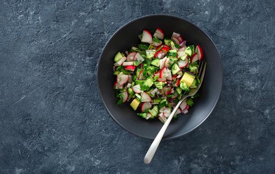 Healthy salad bowl radish cucumber avocado top view