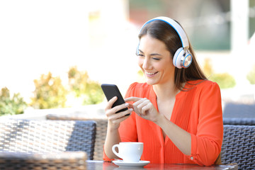 Happy woman listening to music in a coffee shop