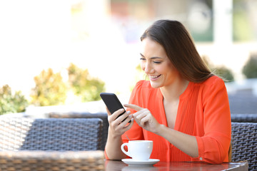 Happy woman is browsing a smart phone in a coffee shop