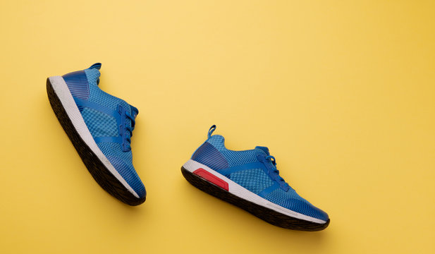 A studio shot of pair of running shoes on yellow background. Flat lay.