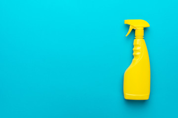 cleaning spray on the turquoise blue background with copy space. flat lay image of yellow plastic dispenser