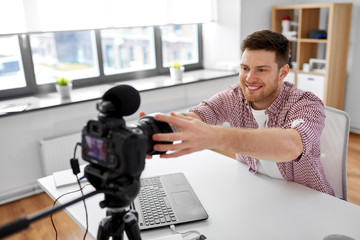 blogging, videoblog and people concept - male video blogger adjusting camera at home office