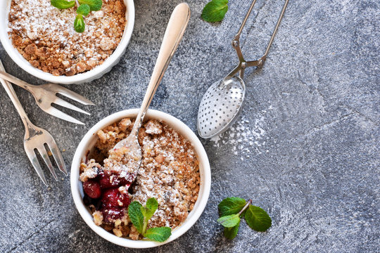 Cherry crumble with nuts and mint on a concrete background.