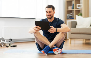 sport, fitness and healthy lifestyle concept - man with tablet computer sitting on exercise mat at home