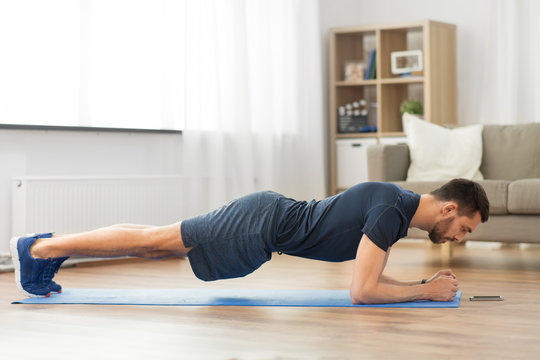 sport, fitness and healthy lifestyle concept - man looking at smartphone and doing plank exercise at home