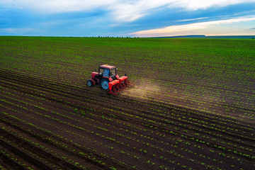 Tractor cultivating field at spring, aerial top drone view Wall mural