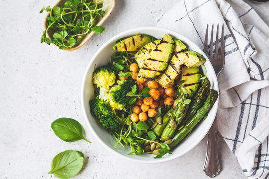 Buddha bowl with grilled avocado, asparagus, chickpeas, pea sprouts and broccoli.