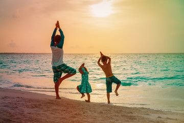 father with kids exercise at sunset beach, family doing yoga