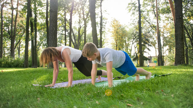 Photo of middle aged female yoga teacher or guru teaching teenage boy doing yoga. Woman with boy meditating and stretching on grass at park