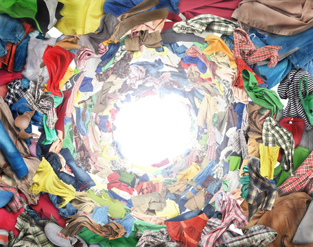 Sale concept. Top view to vortex of clothes. Donation.