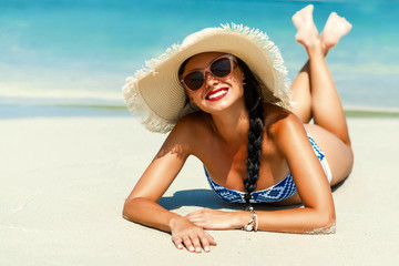 Journey. Young beautiful lady in a straw hat, sunglasses is lying on the sand of the sea shore smiling, resting, traveling