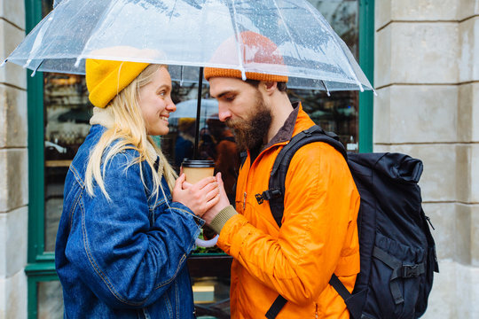 Stylish hipster couple with transparent umbrella in bright casual clothes in city street drrinking hot coffee. Beard man and blonde woman over window outdoor. Lifestyle love concept.