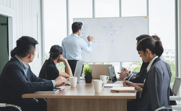 Businessman leader writing on the whiteboard present business marketing graph while meeting with colleagues in office.Business Team Meeting Presentation,Conference Planning Business Concept