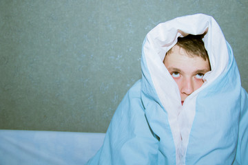 young guy sitting on a bed wrapped in a blue blanket