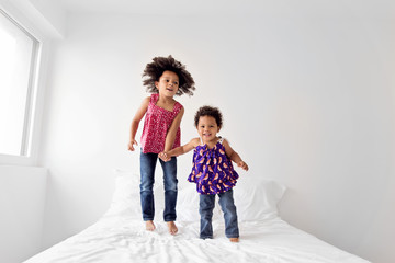 Little girl with afro hair and her baby sister jump on bed