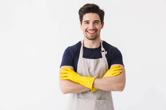 Photo of happy young man wearing yellow rubber gloves for hands protection smiling at camera while cleaning house