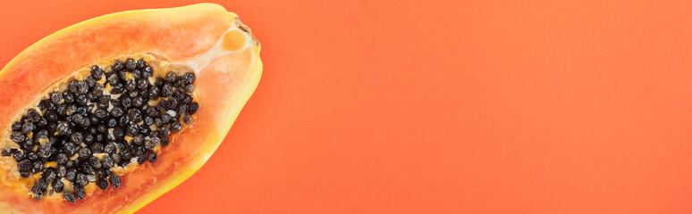 panoramic shot of ripe exotic papaya half with black seeds isolated on orange