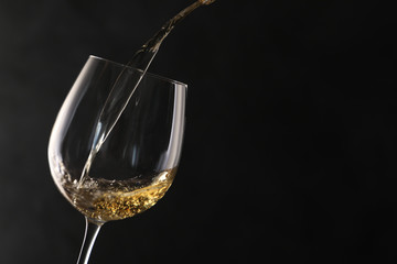 Spoed Foto op Canvas Alcohol Pouring white wine into glass on dark background. Space for text