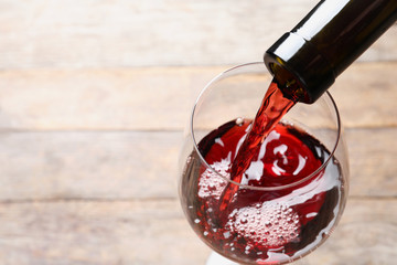 Papiers peints Alcool Pouring red wine from bottle into glass on blurred background, closeup. Space for text
