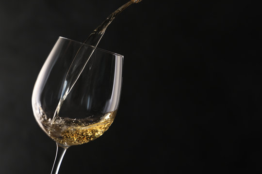 Pouring white wine into glass on dark background. Space for text