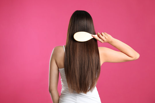 Back view of young woman with hair brush on color background