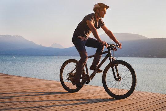 man cycling on bicycle near beautiful mountain lake, leisure biking sport activity outdoors