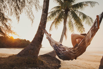 tourist relaxing in hammock on tropical beach with coconut palm trees, relaxation and leisure tourism Wall mural