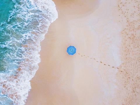creative colorful shot of beach umbrella near ocean wave from above, minimalist landscape