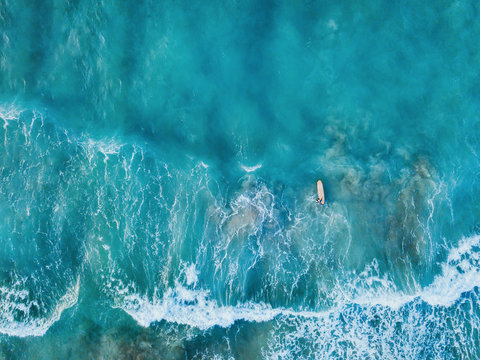aerial top down view of surfer with surf board in ocean wave from drone