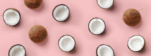 Pattern with ripe coconuts on pink background. Top View. Copy Space. Pop art design, creative summer concept. Half of coconut in minimal flat lay style