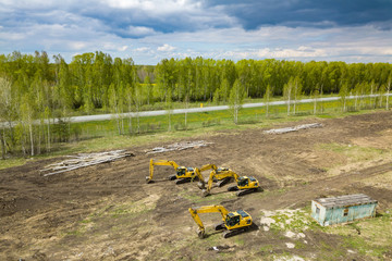 Aerial top view of four yellow crawler excavators standing on ground near the construction site and waiting to start digging the ground near the road in field among tree under the coulds and gray sky