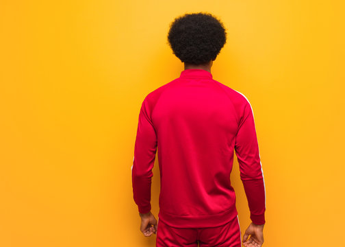 Young sport black man over an orange wall from behind, looking back