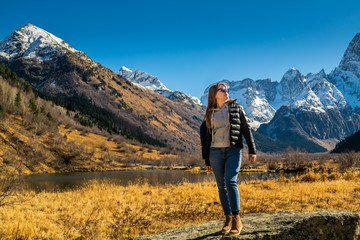 Beautiful young russian woman in front of autumn landscape with mountain lake Tumanly-kel, the Mist lake, located in Russia, near Dombay , in Caucasus mountains, Gonachkhir gorge