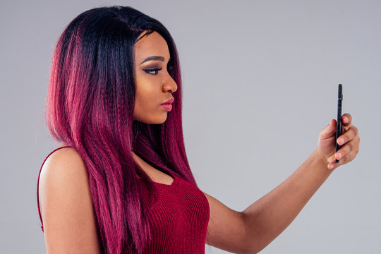 african american beautiful woman creative hair coloring dye purple color making selfie photo on camera smartphone on white background in studio