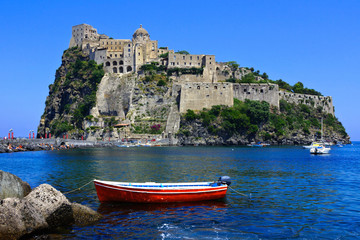 Aragonese Castle with boat in the blue waters off the island of Ischia, Italy