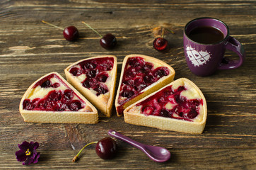 Set of mini tarts with cherries and cream with cup of black tea on dark wooden background