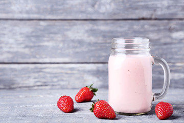 Wall Mural - Smoothie in glass jar with strawberries on grey wooden table