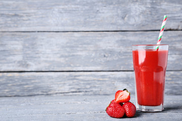 Wall Mural - Smoothie in glass with strawberries on grey wooden table