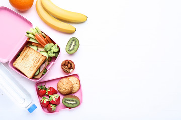 School lunch box with sandwich and berries on wooden table