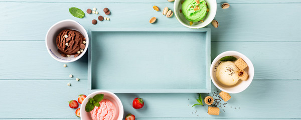 Flat lay, overhead shoot of homemade assorted ice cream on light blue wooden background. Healthy summer food concept. Top view, copy space, banner.