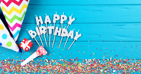 Happy Birthday candles with decorations and sprinkles on wooden table