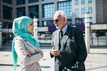 Young beautiful muslim woman with hijab standing in front of modern city building and talking with senior business man. Global investment business concept.