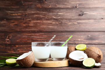Wall Mural - Coconut milk in glasses with limes on wooden table