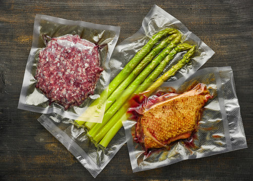 Duck breast, burger meat and asparagus vacuum sealed on wooden table ready for sous vide cooking, from above