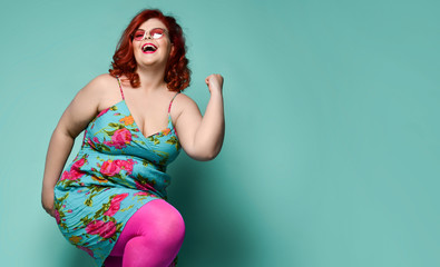 Happy dancing plus-size lady overweight woman in hat, sunglasses and colorful clothes shows Yes sign with her arm