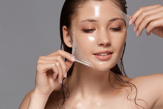 female with wet hair and naked shoulders removing trasparent peeling mask and looking down, copy space, woman facial treatment