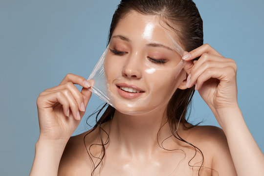 young and happy woman removes facial mask and looking down to the side, female skin care, copy space, cosmetology treatment
