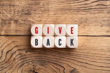 """Würfel mit Aufschrift """"GIVE BACK"""" auf Holzuntergrund"""