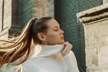Fashionable woman with long hair in ponytail hairstyle wearing trendy hoop earrings, white turtleneck sweater, posing in street of European city. Copy, empty space for text